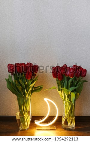Neon moon sign with beautiful red tulips. Trendy style. Floral background. Neon sign. Custom neon. Home decor.