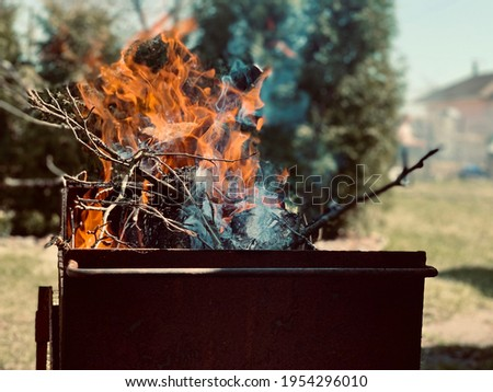 Flame of fire and wood, tree branches. Burning fire in an iron barbecue. A large bonfire made of planks. Firewood in a bright flame against the blue sky.
