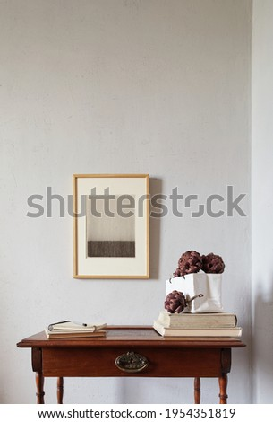 Wooden frames mockup. Dry decorative artichokes in a vase on an old wooden desk. Composition on a white wall background