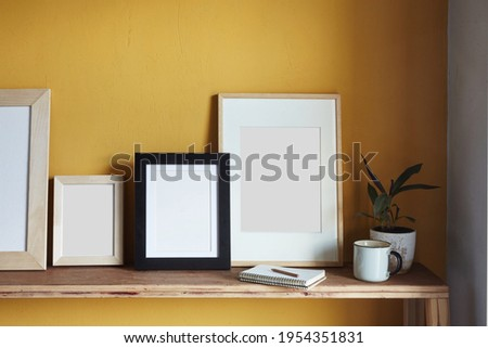 Modern graphics on a yellow background. Composition with a flowerpot, dried artichokes, a notebook and a cup. Against the background of a yellow wall