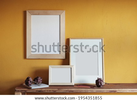 Wooden frames mockup. Composition with a dried artichokes, and book . Against the background of a yellow wall