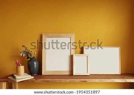 Wooden frames mockup. Composition with a flowerpot, dried artichokes, a notebook and a cup. Against the background of a yellow wall