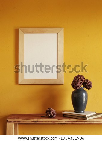 Wooden frames mockup. Dry decorative artichokes in a vase on an old wooden shelf. Composition on a yellow wall background