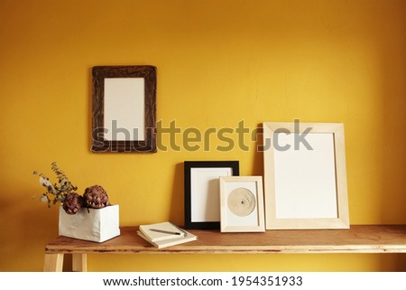Wooden frames mockup. Composition with a flowerpot, dried artichokes, a notebook . Against the background of a yellow wall