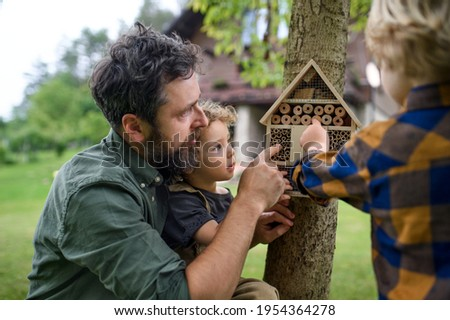Small children with father holding bug and insect hotel in garden, sustainable lifestyle. Royalty-Free Stock Photo #1954364278