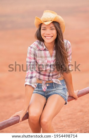 Cowgirl Texas woman smiling happy on country farm ranch wearing cowboy hat , western shirt and jeans shorts. Young multiracial Asian American rancher girl in desert countryside. Vertical portrait.