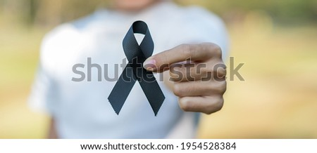 Melanoma and skin cancer, Vaccine injury awareness month and rest in peace concepts. Woman holding black Ribbon Royalty-Free Stock Photo #1954528384