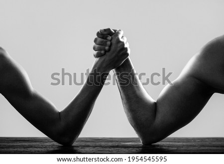 Arms wrestling thin hand and a big strong arm in studio. Arm wrestling. Heavily muscled man arm wrestling a puny weak man. Two man's hands clasped arm wrestling, strong and weak. Black and white.