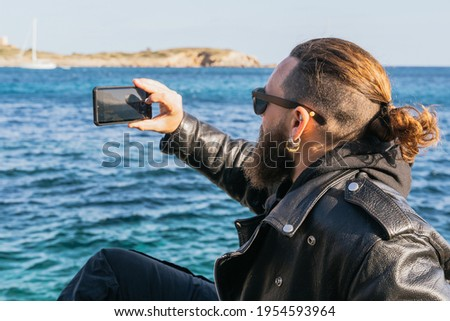 Caucasian man with beard, long hair and sunglasses sitting by the sea at sunset and taking a photo with his smartphone in a cove in Portals. Palma de Mallorca, Spain (Copyspace)