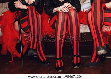 Close-up of legs of circus performer in suit and striped red-black stockings in dressing room. Circus performer waiting for an invitation to enter stage or arena. Concert performance for backgrounds Royalty-Free Stock Photo #1954671304