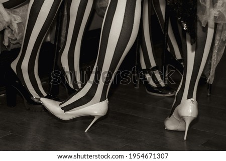 Close-up of legs of circus performer in suit and striped red-black stockings in dressing room. Circus performer waiting for an invitation to enter stage or arena. Concert performance for backgrounds Royalty-Free Stock Photo #1954671307