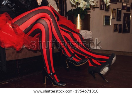 Close-up of legs of circus performer in suit and striped red-black stockings in dressing room. Circus performer waiting for an invitation to enter stage or arena. Concert performance for backgrounds Royalty-Free Stock Photo #1954671310