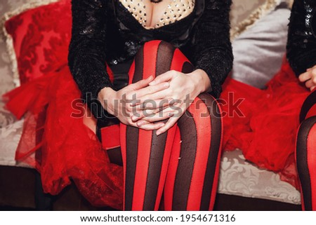 Close-up of legs of circus performer in suit and striped red-black stockings in dressing room. Circus performer waiting for an invitation to enter stage or arena. Concert performance for backgrounds Royalty-Free Stock Photo #1954671316
