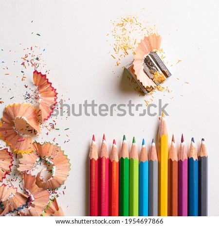Top view of the colored pencils side by side highlighting the yellow pencil on the white background. With colored pencil shavings on the left and a pencil sharpener on the upper right.