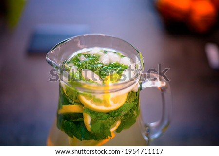 Close up photo of ice cold lemonade with mint and lemon. The pitcher is standing on the kitchen counter. Background is blurred. It is good in summer and winter.