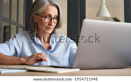 Mature adult 60s aged woman working at laptop watching video conference webinar training, virtual meeting. Business lady e learning online computer classes, typing, seniors and remote education.