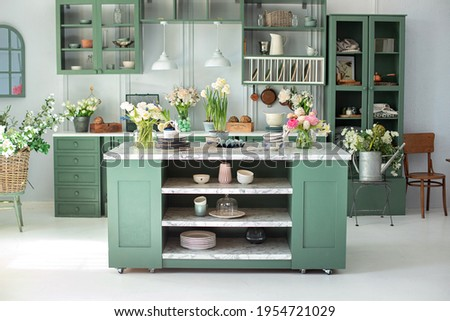 Green kitchen interior with furniture. Stylish cuisine with flowers in vase. Wooden kitchen in spring decor. Cozy home decor. Kitchen utensils, dishes and plate on table. kitchen island in dining room Royalty-Free Stock Photo #1954721029