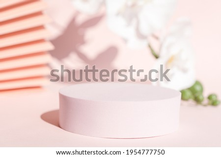 Podium stand pedestal for product presentation, coral pink mockup for branding and packaging. Modern design, pastel color backdrop, flowers and fan. Feminine scene for cosmetic display. Copy space. Royalty-Free Stock Photo #1954777750