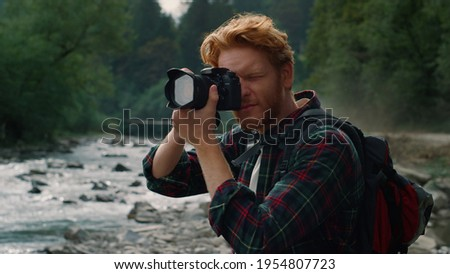 Focused man taking photos on professional camera in mountains. Male photographer adjusting zoom on camera lens and photographing at mountain river bank. Young hiker using photo camera outdoor