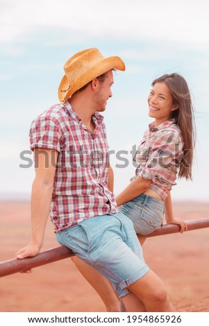 Couple people in western outfits portrait in american countryside farm. Asian woman smiling to young rancher, interracial American couple. Man wearing cowboy hat and Asian woman wearing plaid shirt.