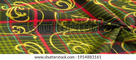 Thick cotton checkered fabric Yellow-red green black stripes on the fabric. Decorated with gold monograms. Texture, background, pattern.
