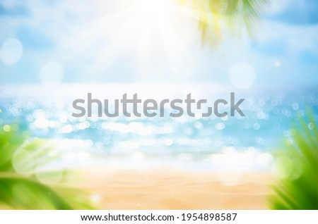 Blur beautiful nature green palm leaf on tropical beach with bokeh sun light wave abstract background. Copy space of summer vacation and business travel concept. Vintage tone filter effect color style Royalty-Free Stock Photo #1954898587