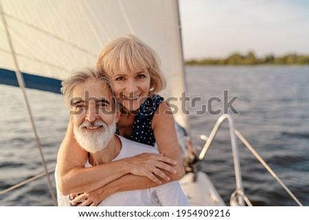 Romantic vacation and luxury travel. Senior loving couple sitting on the yacht deck. Sailing the sea. Royalty-Free Stock Photo #1954909216