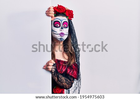 Young woman wearing day of the dead custome holding blank empty banner puffing cheeks with funny face. mouth inflated with air, crazy expression.