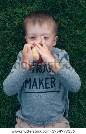 A boy fools and eats an apple, lieing on the grass. He wears longsleave with a sign Trouble maker.