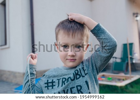 A boy is scratching his head. He wears longsleave with a sign Trouble maker.