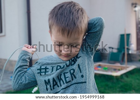 A boy in the yard is thinking. He wears longsleave with a sign Trouble Maker.