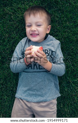 A boy is laughing and eating an apple. He wears longsleave with a sign Trouble maker.