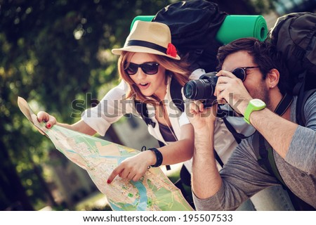 Two Young Tourists With Backpacks Sightseeing City