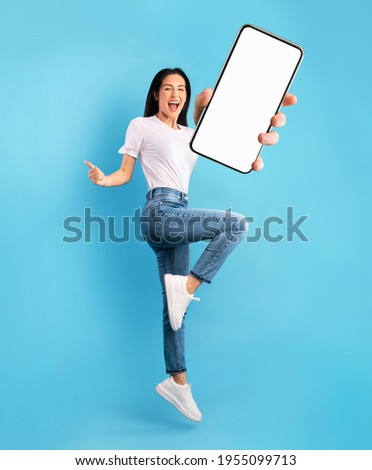 Advertisement for mobile application. Excited young lady jumping over blue studio background, showing modern smartphone with empty screen, mockup for app. Collage Royalty-Free Stock Photo #1955099713