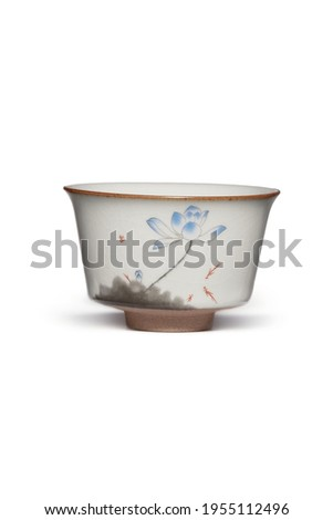 Subject shot of white ceramic bowl with crazing and decorated with picture of blue lotus flower painted in Chinese style. Graceful tea bowl is isolated on the white background.