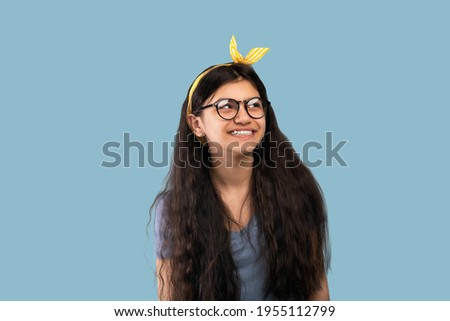 Pretty Indian teen girl with long hair and headband smiling on blue studio background. Portrait of attractive teenage lady in casual wear and glasses posing and having fun Royalty-Free Stock Photo #1955112799