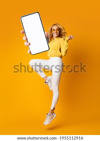 Cheerful blonde woman jumping up and showing newest smartphone with empty screen, enjoying new application for mobile device. Orange studio background, creative collage with mockup Royalty-Free Stock Photo #1955112916
