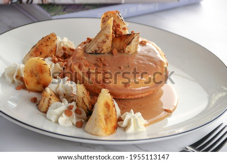 Delicious Fluffy banana pancakes with sauce and banana fruit in the top on white background