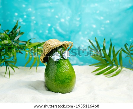 Avocado in hat and sunglasses  relaxes  on  beach. Summer tropical minimal humor poster.