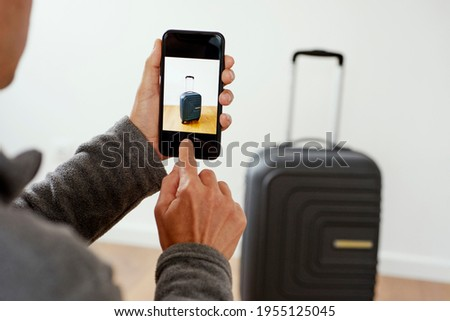 closeup of a young caucasian man taking a picture, with his smartphone, of a suitcasen to sell it on an online marketplace app to sell and buy secondhand goods