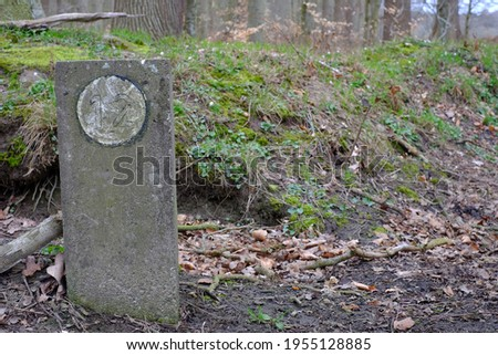 A boundary stone marks the forest boundary Royalty-Free Stock Photo #1955128885