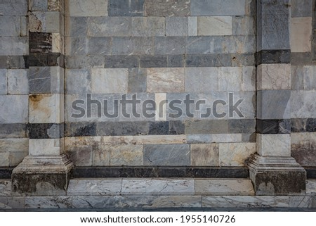 View of facade detail - wall of Primatial Metropolitan Cathedral of the Assumption of Mary in Piazza del Duomo in Pisa Royalty-Free Stock Photo #1955140726