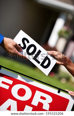 Home: Agent Giving Sold Sign To House Owner