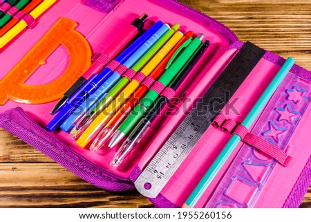 Different school stationeries (pens, pencils, ruler and protractor) in pink pencil box