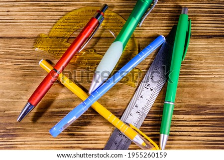 Multi colored ball pens, protractor and ruler on rustic wooden table. Top view