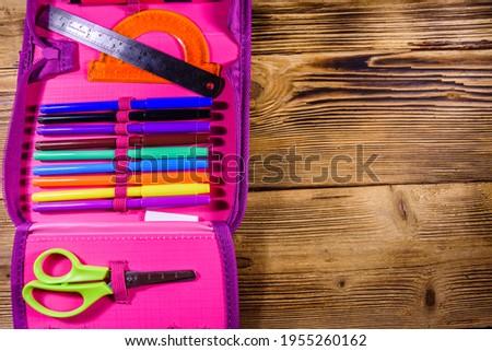 Different school stationeries (pens, pencils, scissors, felt tip pens, ruler and protractor) in pink pencil box. Top view