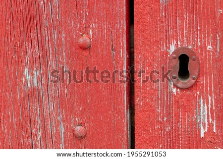 A closeup of a bright red vintage metal keyholder in a textured red wooden door. The exterior of the old woodshed has worn and wear patterns with some scuff marks.  Royalty-Free Stock Photo #1955291053
