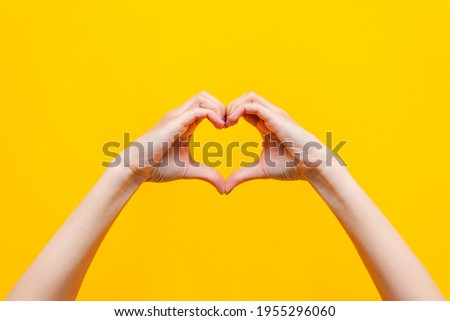 Female hands showing a heart shape isolated on a bright color yellow background. Sign of love, harmony, gratitude, charity. Feelings and emotions concept Royalty-Free Stock Photo #1955296060