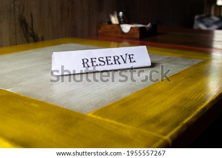 The flying around the plate is reserved, which stands on the wooden table in the restaurant. Reservation of a place in the cafe. Seat reservation. Reserving a table in the institution in advance. Royalty-Free Stock Photo #1955557267