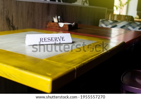 The flying around the plate is reserved, which stands on the wooden table in the restaurant. Reservation of a place in the cafe. Seat reservation. Reserving a table in the institution in advance. Royalty-Free Stock Photo #1955557270